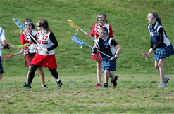 A photo of young women playing Lacrosse on a Farragut athletic field.