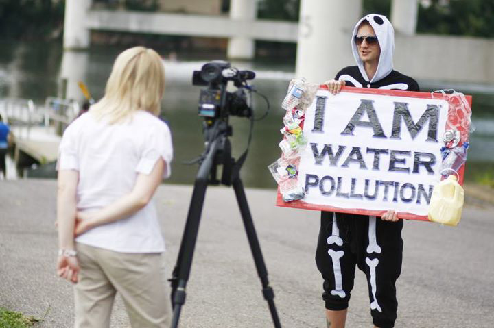 "americorps member, Josh, dressed up as a skeleton and holding a sign stating ""i am water pollution"""