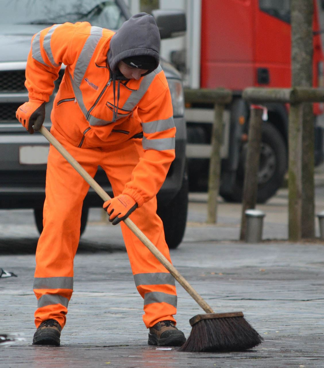 man wearing an orange suit sweeping a roadway to remove debris